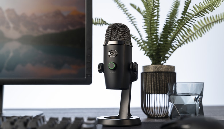 Ein USB-Mikrofon mit einem Tischstativ auf einem Schreibtisch platziert; im Hintergrund ein Monitor, eine Tastatur sowie eine Pflanze