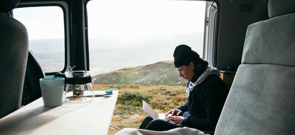 Ein junger Mann sitzt in einem Van in der Natur, einen Laptop auf dem Schoß und eine Mütze auf dem Kopf. Eine Kaffeekanne und -becher im Vordergrund auf dem Tisch im Auto.
