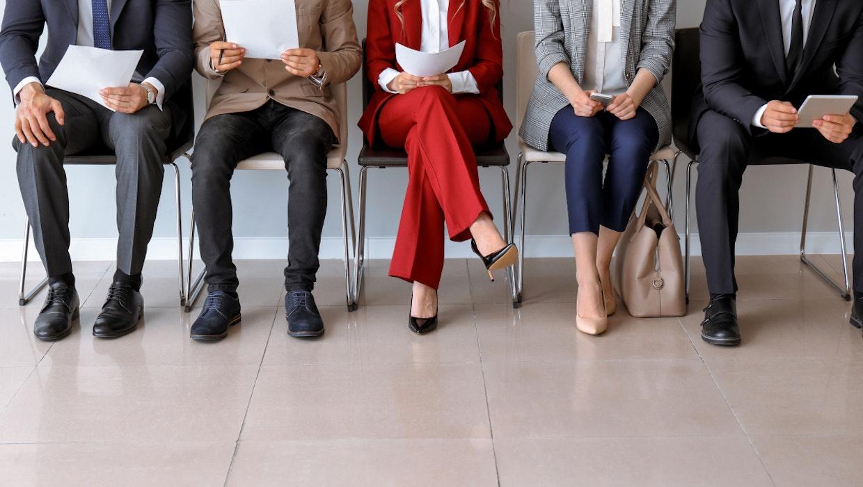 Familienfreundlichkeit bei Unternehmen? Zwei Hände –  auf der einen steht eine Frau mit Baby, auf der anderen sitzt sie am Schreibtisch.