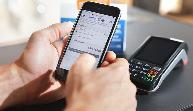 Das Bild zeigt eine Handyzahlung mit ratenkauf an der Ladenkasse. Im Hintergrund sieht man das Kartenterminal.