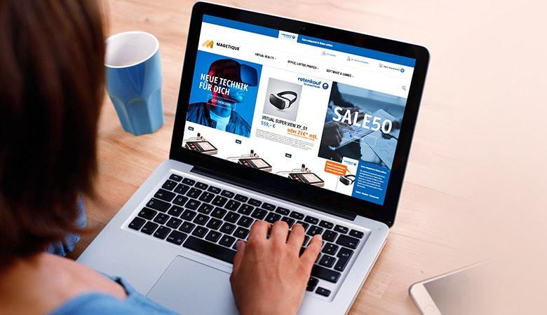 Man schaut über die Schulter einer Frau auf ihren Laptop. Das Bild zeigt einen generischen Onlineshop mit einem großen Sale. Links neben dem Laptop steht eine leere Kaffeetasse.